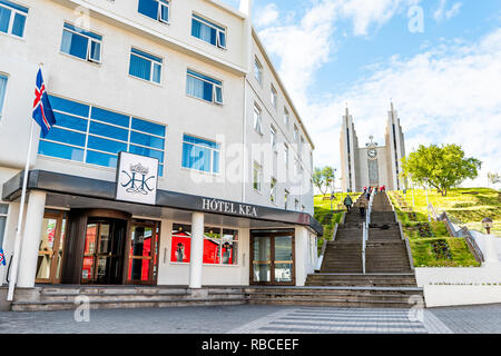 Akureyri, Iceland - June 17, 2018: Cityscape streetscape street in town village city with people on steps to famous church on hill and Hotel Kea with  - Stock Photo