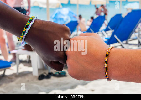 Two fists of two different ethnicity people with braided bracelets from colored threads on each of the wrists touching each other in a friendship and  - Stock Photo