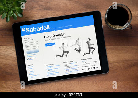 The website of Banco Sabadell is seen on an iPad tablet, on a wooden table along with an espresso coffee and a house plant (Editorial use only). - Stock Photo