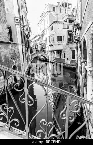 Typical Gondola in a narrow Venetian canal. Traditional italian architecture. Black and white image. - Stock Photo