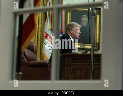 President Donald Trump deliver a televised address to the nation from the Oval Office at the White House in Washington, DC on January 8, 2019. Photo taken through the Oval Office windows. The speech comes on the 18th day of a partial government shutdown cause by a dispute over a proposed border wall separating the United States and Mexico. Credit: Kevin Dietsch/Pool via CNP | usage worldwide - Stock Photo