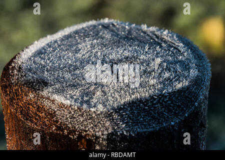 Frost on the top of a wooden fence post - Stock Photo
