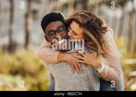 Handsome young man giving piggyback ride to his girlfriend. Couple having fun outdoors. Man carrying his girlfriend on his back, with woman kissing ma - Stock Photo
