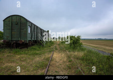 Abandoned railway wagons with old railway track in the middle of the countryside - Stock Photo