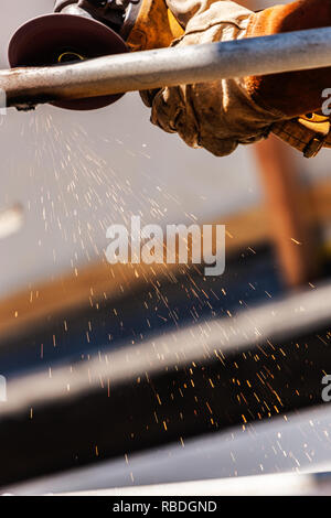 Welder At Shipyard Using Rotary Grinder On Metal Pipe - Stock Photo