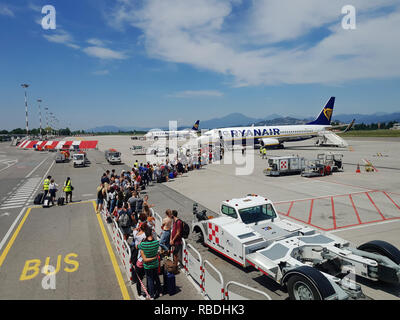 Passengers walking on tarmac of Milan Bergamo Airport. Travelers with luggage at apron area of Orio al Serio airport ready to board a Ryanair aircraft - Stock Photo