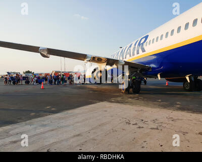 Passengers board on tarmac of Thessaloniki airport. Travelers at apron area of Makedonia airport, boarding from front entrance of a Ryanair aircraft. - Stock Photo