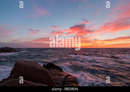 Pink sky at sunset on the waves crashing on cliffs Capo Testa Santa Teresa di Gallura Province of Sassari Sardinia Italy Europe - Stock Photo