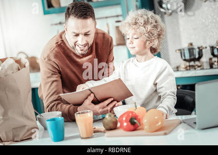 Good mood. Handsome blonde boy expressing positivity while being in all ears, going to help his dad - Stock Photo