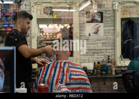 Hairdresser putting the finishing touches to a mans haircut with an electric trimmer at salon in Leeds Market,West Yorkshire,England,UK. - Stock Photo
