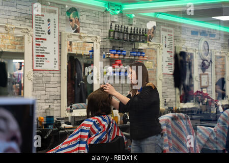 A woman Hairdresser cutting a clients hair with a pair of scissors at a salon in Leeds Market,West Yorkshire,England,UK. - Stock Photo