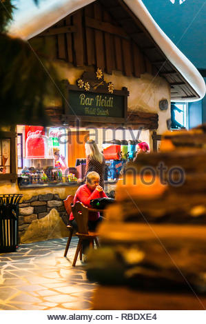 Kownaty, Poland - January 6, 2019: Woman ordering at the Bar Heidi stand in the Majaland attraction park. - Stock Photo