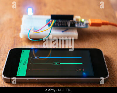 RGB Led on a breadboard with microcontroller board being controlled by a mobile phone app. - Stock Photo