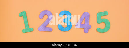 Bright, baby rooms from 1 to 5 are made of colored baby foam isolated on peach background. colored numbers. - Stock Photo