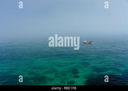 Fisherman boat on misty sea - Stock Photo