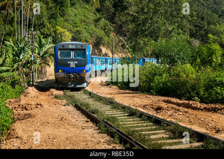 Long distance commuter train heading out of Ella, Sri Lanka passing through a cutting. - Stock Photo