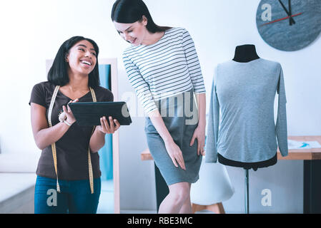 Good joke. Smiling pretty girl showing something on her tablet to her friend - Stock Photo