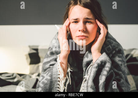 Subject disease and treatment. young Caucasian woman sits home bedroom bed wrapped in body blanket with high fever, fever holds strong headache behind - Stock Photo
