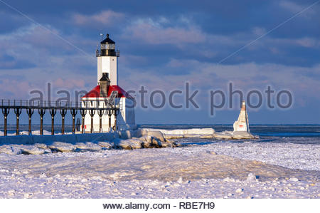 Michigan City, Indiana lighthouse and outer pier marker covered in snow and ice and surrounded by a frozen Lake Michigan - Stock Photo