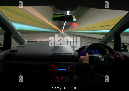 Traffic nighttime trails on motorway with headlights and light trails on dartford tunnel - Stock Photo