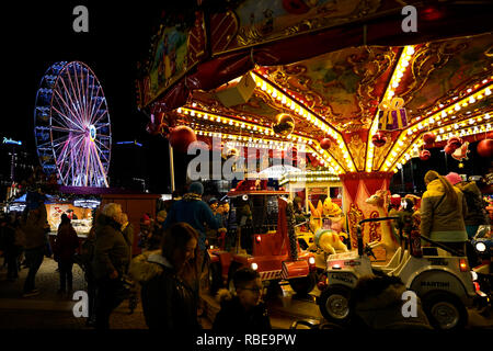 A ferris wheel and a carousel are just some of the attractions at the Christmas Market in the city center of Leipzig. Saxony, Germany, Europe - Stock Photo