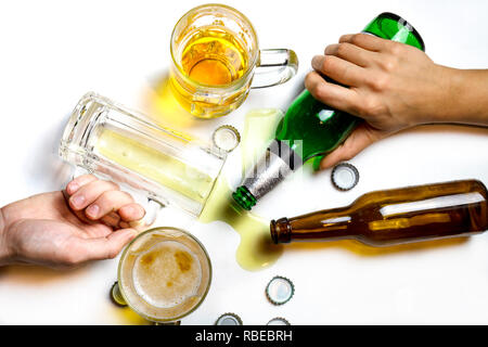 When the party is over oncept. Hands of people passed out on messy table after beer party - Stock Photo
