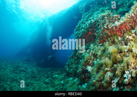 Panoramic view of a scuba diver crossing the underwater arch of El Arco dive site in Ses Salines Natural Park (Formentera, Balearic Islands, Spain) - Stock Photo