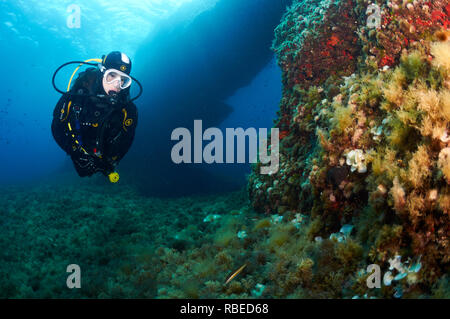Female scuba diver fitted with Aqua Lung diving equipment near an underwater arch in Ses Salines Natural Park (Formentera, Balearic Islands, Spain) - Stock Photo