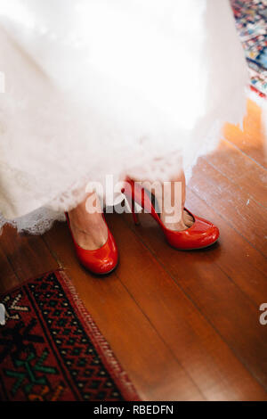 bride in wedding dress putting on red shoes - Stock Photo