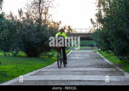 Valencia, Spain - January 06, 2019:  Policewoman on a bike patroling park in a dry river Turia in Valencia city. Valencia Police. - Stock Photo