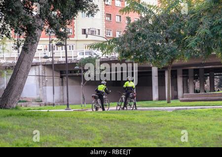 Valencia, Spain - January 06, 2019:  Policewoman and Policeman on bikes patroling park in a dry river Turia in Valencia city. Valencia Police. - Stock Photo