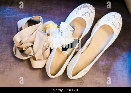 woman's wedding shoes sitting on ground