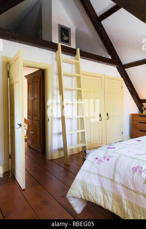 Partial view of the king size bed and old wooden ladder leading to the attic in the master bedroom on the upstairs floor inside an old home - Stock Photo