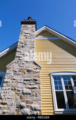Natural stone chimney on the exterior wall of a yellow cladded with white trim contemporary country style residential home - Stock Photo