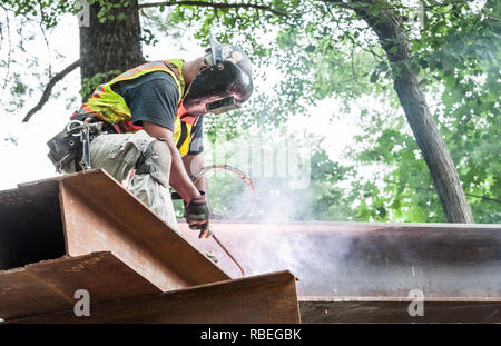 A worker welding a piece onto the new train bridge in Concord, MA - Stock Photo