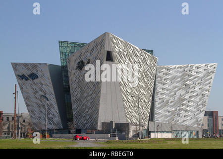 Modern building Belfast. Red car outside Titanic Belfast as seen from the River Lagan. - Stock Photo