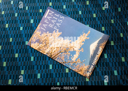 Japan Rail Pass on the seat cover of a train seat - Stock Photo