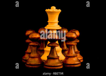 Under siege. White Queen beset by black enemy pawns with sense of no escape, standard chess wooden piece on black background - Stock Photo