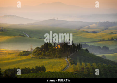 Famous house il Belvedere surrounded by cypress trees in the morning fog in Val d' Orcia valley at sunrise in San Quirico d' Orcia in Tuscany, Italy. - Stock Photo
