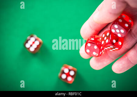 Throwing red poker dices on casino green table. - Stock Photo