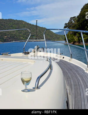 A Glass of Sauvignon Blanc Wine on the deck of a Luxury Motor Boat in the Marlborough Sounds New Zealand. - Stock Photo