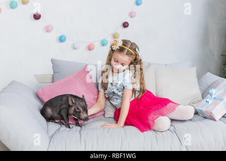 Chinese New Year 2019. Lucky Pig. The year of the pig. Cute blonde girl with baby pig celebrating Chinese New Year. 2019 Zodiac. Traditional Chinese holiday.Chinese calendar for the year of pig.Greeting card - Stock Photo