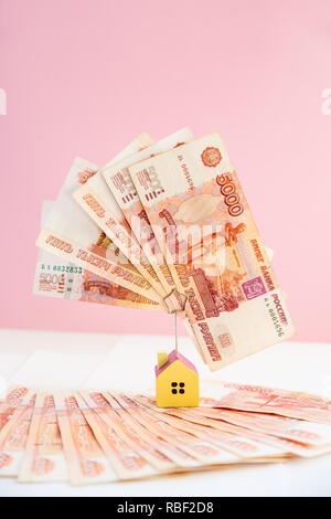 Mortgage loading real estate property with loan money bank concept.money and miniature house model isolated on pink background.Business, finance,saving money,banking ,house loan or insurance concept.russian money. - Stock Photo