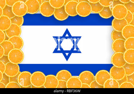 Israel flag  in frame of orange citrus fruit slices. Concept of growing as well as import and export of citrus fruits - Stock Photo