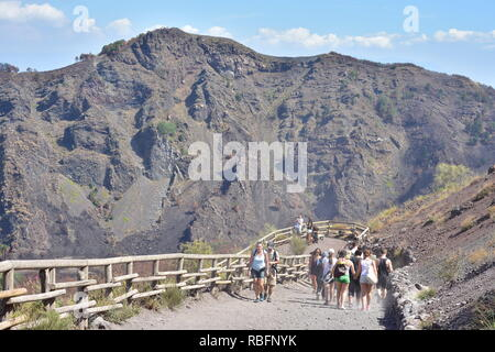 Group of tourists walking up dusty path with wooden railing to summit of Vesuvius volcano on hot summer day. - Stock Photo