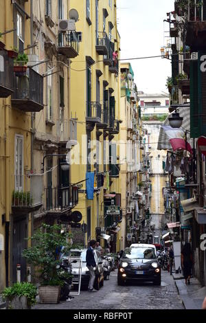 Narrow dark street with cobble stones pavement of historical Naples downtown with typical Mediterranean apartment houses with tiny balconies and woode - Stock Photo