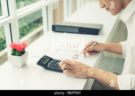 Asian business man using a calculator to calculate the numbers on his desk. Accountant calculating finances. - Stock Photo