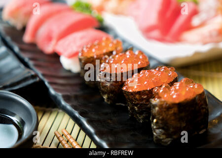 Sushi with chopsticks and soy sauce. Sushi roll japanese food in restaurant. Salmon roe Sushi set with salmon, vegetables, flying fish roe and caviar  - Stock Photo