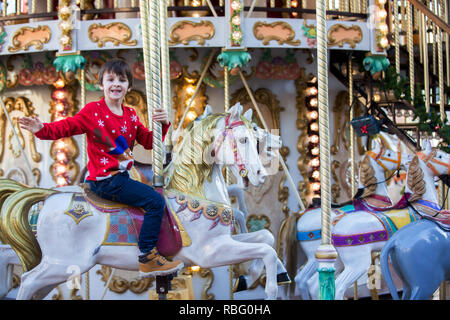 Sweet boys, brothers, riding in a Santa Claus sledge on a merry-go-round, carousel attraction in Europe, active children, wintertime