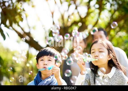 little asian kids boy and girl sister and brother blowing bubbles in a park with parents watching from behind. Stock Photo
